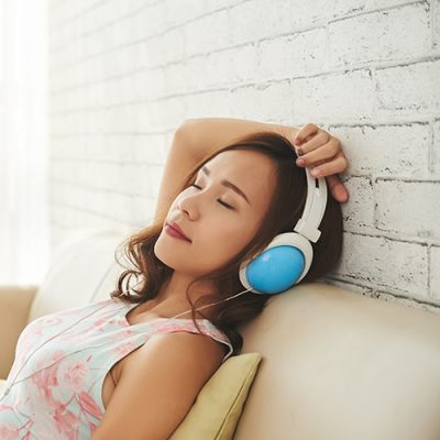 Lovely woman relaxing on sofa with headphones on her head