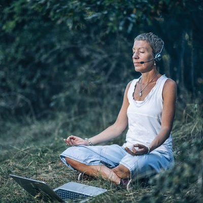 Online meditation. Personal development trainer meditating with her clients over the Internet